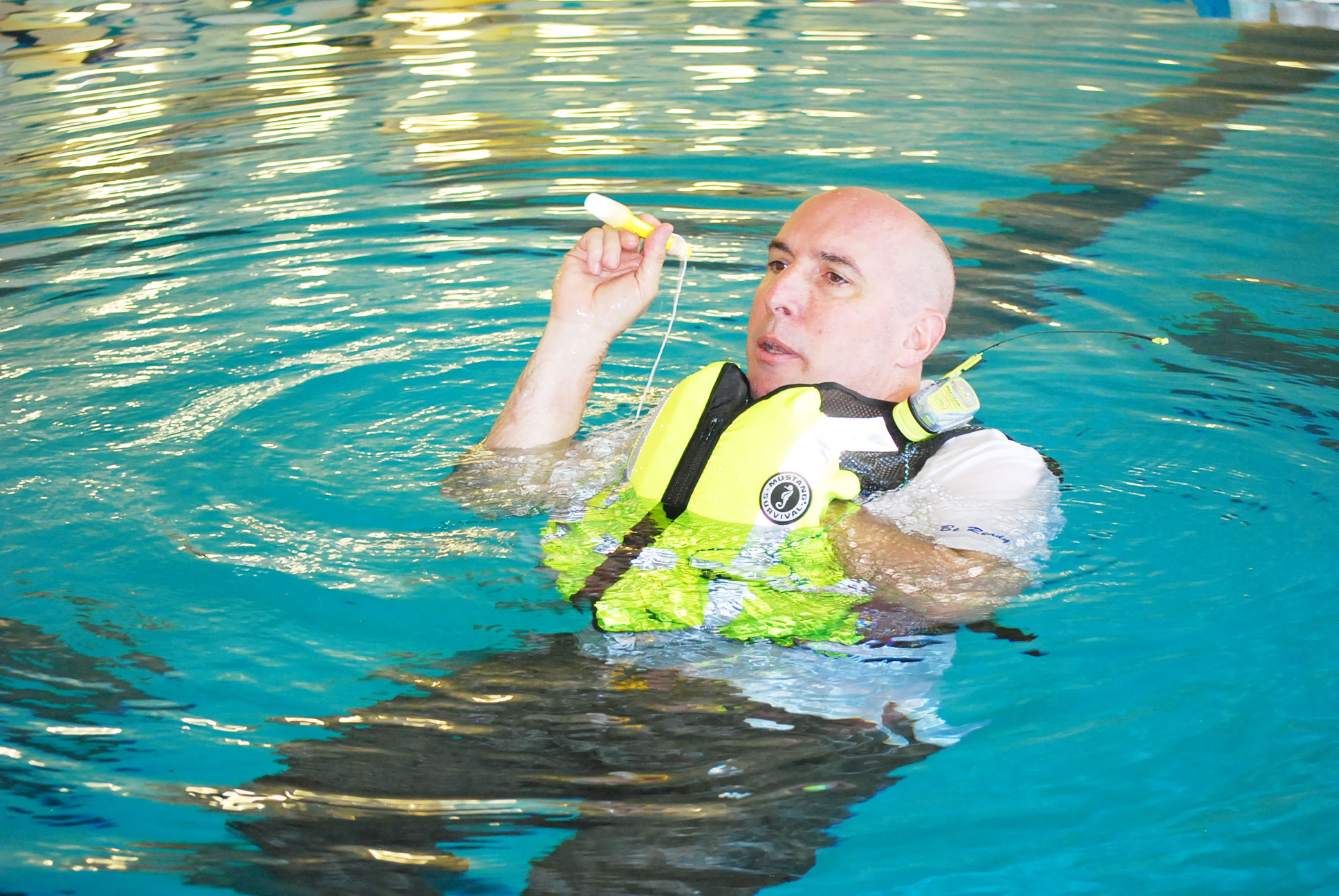 man in water with life jacket waving flashlight