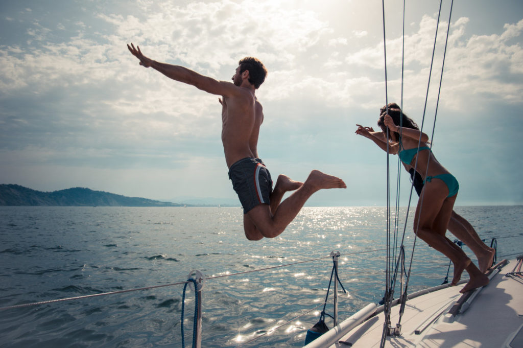People jumping off a sailboat to swim.